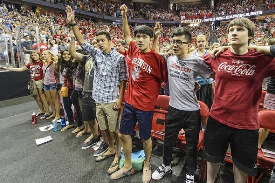 """First year students lock arms and sign """"Varsity"""" during the Chancellor's Convocation for new students, a Wisconsin Welcome event held at the Kohl Center at the University of Wisconsin-Madison on Sept. 1, 2015. (Photo by Bryce Richter / UW-Madison)"""