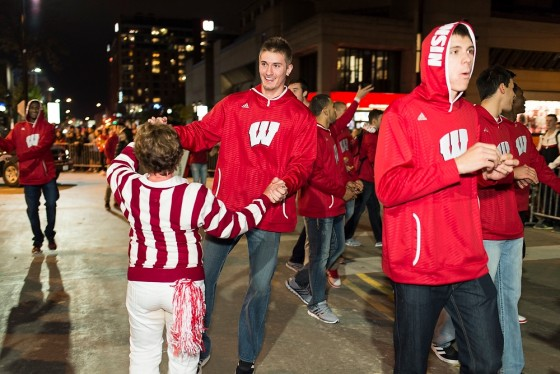 Wisconsin men's basketball player Aaron Moesch dances with a member of the UW Alumni Cheerleading Association as thousands of spectators line State Street during the University of Wisconsin-Madison's Homecoming Parade on Oct. 24, 2014. The annual parade is one of many Homecoming week activities sponsored by the Wisconsin Alumni Association (WAA). (Photo by Jeff Miller/UW-Madison)