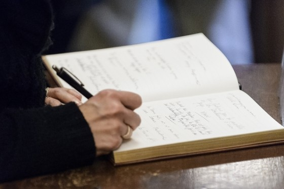Student residents and members of the UW and greater Madison community sign a guestbook that will be delivered to the mayor of Paris during a gathering of solidarity and support for the victims of the Nov. 13th Paris attacks which was held at the French House at the University of Wisconsin-Madison on Nov. 16, 2015. (Photo by Bryce Richter / UW-Madison)