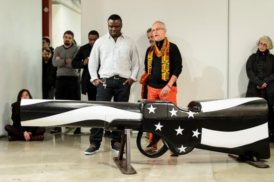 At right, Henry Drewal, professor of art history, introduces Eric Adjetey Anang, Ghanaian woodcarver, master-coffin builder and Windgate Artist in Residence in the Art Department, during an opening exhibit of Adjetey Anang's work at the Arts Loft at the University of Wisconsin-Madison on Nov. 30, 2015. During the event, Adjetey Anang led a gun-breaking ceremony and invited guests to participate in a symbolic breaking of the barrel of his gun-shaped coffin. The gun-breaking action was in support of the Black Lives Matter movement, and against gun violence locally, nationally and internationally. (Photo by Jeff Miller/UW-Madison)