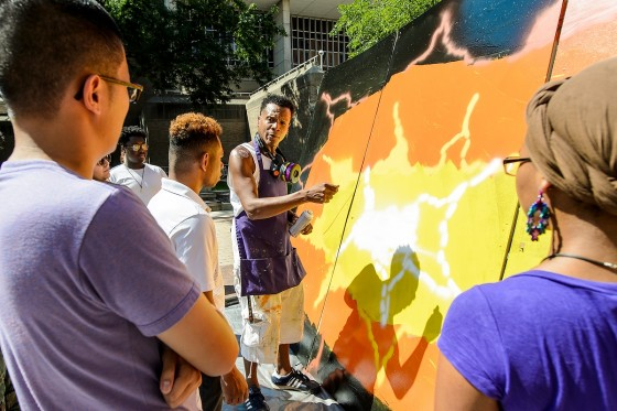 UW students and members of the Madison community participate in a JVN Day Festival event that included activities such as sidewalk chalking and creating a graffiti mural on East Campus Mall at the University of Wisconsin-Madison on Aug. 28, 2016. The JVN Day Festival is an annual event to honor the memory of UW-Madison student John Vietnam Nguyen who drowned while trying to save a friend on Lake Mendota.  Pictured here, Chicago graffiti artist Lavie Raven (center), gives a demonstration of aerosol painting techniques. (Photo by Bryce Richter / UW-Madison)