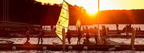 Hoofer Sailing Club members bring their windsurfing boards and sailboats in for the evening near the Memorial Union Terrace at the University of Wisconsin-Madison as the summer sun sets over a Lake Mendota pier on Aug. 31, 2016. (Photo by Jeff Miller/UW-Madison)
