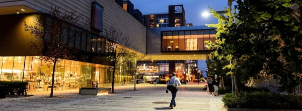 Dusk falls to nighttime as pedestrians walk along East Campus Mall past the Chazen Museum of Art (left) at the University of Wisconsin-Madison during autumn on Oct. 28, 2016. (Photo by Jeff Miller/UW-Madison)