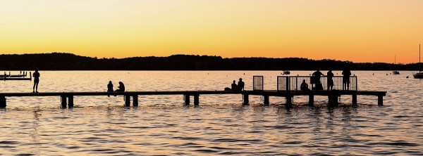 People watch the sun set over Lake Mendota while sitting on the Goodspeed Family Pier near the Memorial Union Terrace at the University of Wisconsin-Madison during autumn on Oct. 18, 2016. On the horizon is Picnic Point. (Photo by Jeff Miller/UW-Madison)