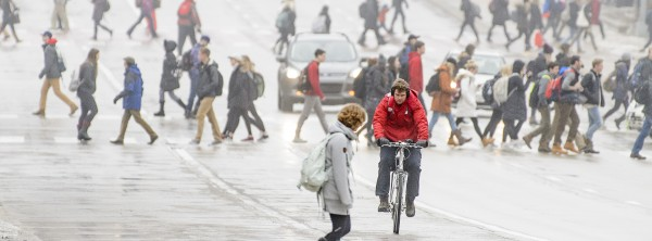 A UW student wearing badger red stands out against the morning fog and pedestrian traffic while riding a bike on University Avenue on the first day of the spring semester at the University of Wisconsin-Madison during winter on Jan. 17, 2017. (Photo by Bryce Richter / UW-Madison)