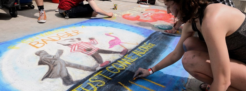 """Undergraduate Stephanie Rink puts the finishing touches on her art project — """"If you wanna be a Badger, just come along with me"""" — as part of Badgers Chalk the Block, an All-Campus Party event held on Library Mall at the University of Wisconsin-Madison on April 25, 2017. The springtime event is sponsored by the Wisconsin Alumni Student Board. (Photo by Jeff Miller/UW-Madison)"""