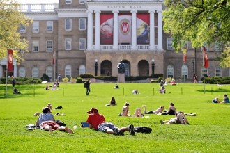 "People relax and study on Bascom Hill at the University of Wisconsin-Madison during spring on May 14, 2013. In the background is Bascom Hall with iconic ""W"" crest banners hanging from the building's columns. (Photo by Jeff Miller/UW-Madison)"